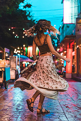 Thailand, Bangkok, young woman in the city dancing on the street at night - p300m1581318 by VITTA GALLERY