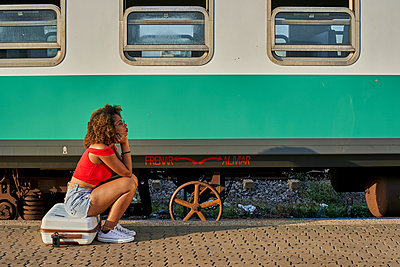 Woman with suitcase sitting at the train station - p300m2103952 von Veam