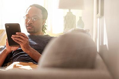 Black man using digital tablet on sofa - p555m1312051 by JGI/Tom Grill
