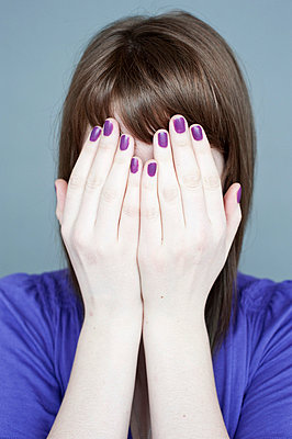Woman with purple nails covering face - p8000025 by Emma McIntyre