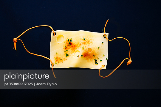 Slice of cheese in the shape of a medical mask - p1053m2297925 by Joern Rynio