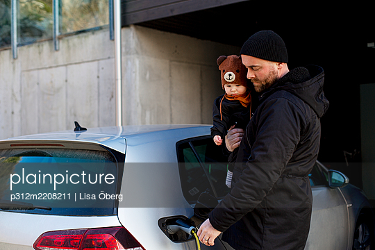 Man charging electric car while carrying baby - p312m2208211 by Lisa Öberg