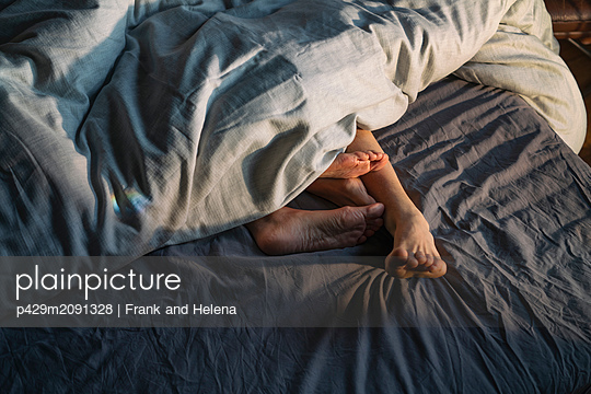Couple's feet sticking out from under duvet in bed - p429m2091328 by Frank and Helena