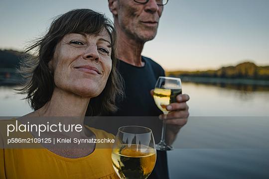 Seniorenpaar trinkt Weißwein am Baldeneysee - p586m2109125 von Kniel Synnatzschke