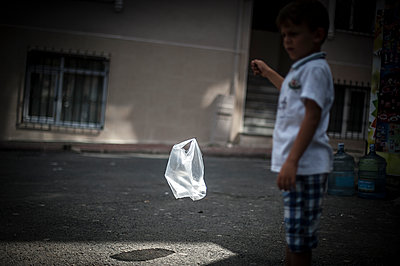 Boy playing with flying plastic bag in sun light - p1007m1134846 by Tilby Vattard