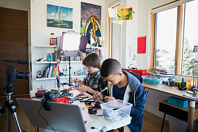 Boys videotaping electronics assembly in bedroom - p1192m1129548f by Hero Images
