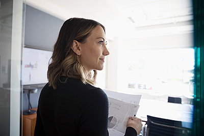 Businesswoman with paperwork looking away in conference room - p1192m1490408 by Hero Images