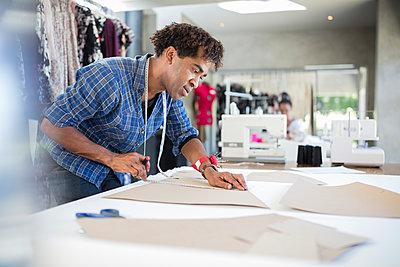 Fashion designer working on draft in studio - p300m1581457 von zerocreatives