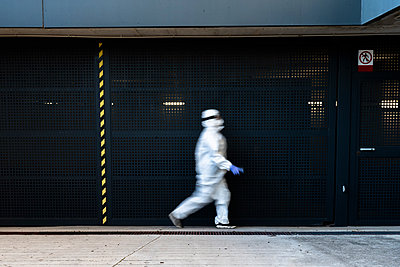 Female scientist wearing protective suit and mask and walking in front of a wall - p300m2170101 by Eloisa Ramos
