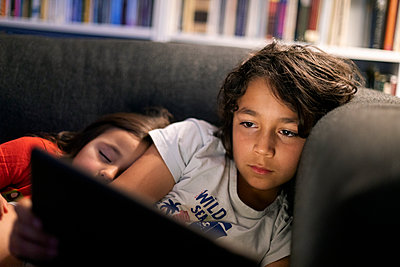 Girl sleeping by brother using digital tablet while relaxing on sofa at home - p300m2203142 by Valentina Barreto