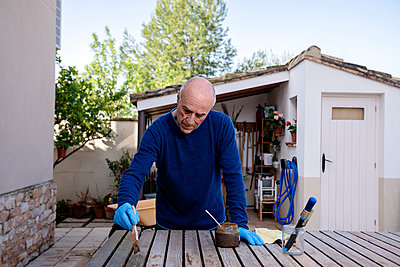 Retired man painting wooden plank at back yard - p300m2273582 by Albert Martínez