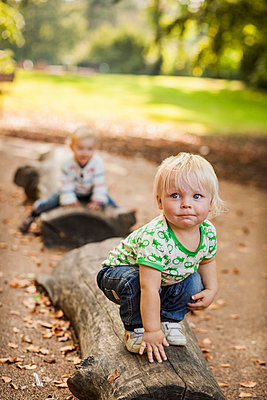 Baby boy looking away while crouching on log at park - p426m977519f by Astrakan