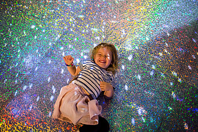 Caucasian girl laying on floor under disco ball - p555m1532433 by Adam Hester