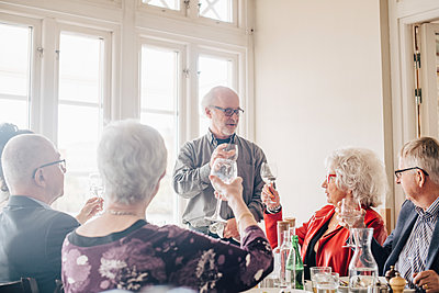 Senior friends with wineglass toasting in restaurant - p426m2149132 by Maskot