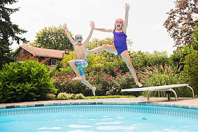 Caucasian children jumping into swimming pool - p555m1421666 by JGI/Jamie Grill