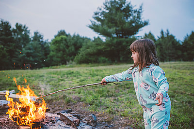 Young girl toasting marshmallow in fire - p924m1547506 by Jenn Austin-Driver (Photography)