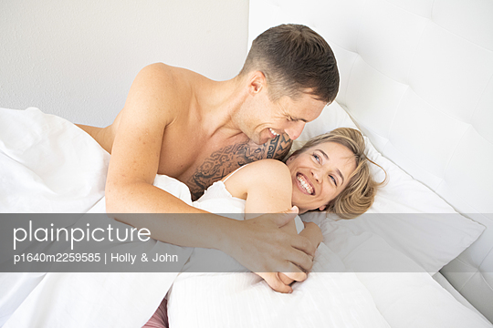 Couple in love embracing in bed - p1640m2259585 by Holly & John