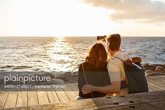 Rear view of couple taking selfie on smart phone while sitting against sea - p426m2149077 by Kentaroo Tryman