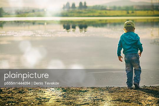 Boy watching ripples in lake - p555m1444094 by Denis Tevekov