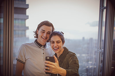 Happy young couple taking selfie at highrise window - p1023m2212493 by Tom Merton