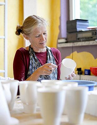 Woman working on mug in porcelain workshop - p300m2005681 by Bernd Friedel