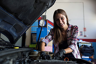 Young casual woman smiling at camera while fixing car engine and working in car service - p300m2155105 by Andrés Benitez