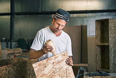 Carpenter applying glue on wooden plank at workshop - p426m1062635f by Maskot