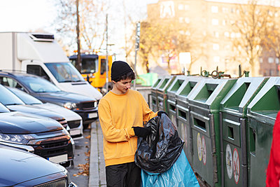 Young male volunteer holding waste in plastic bag by garbage can - p426m2213414 by Maskot