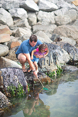 Father and daughter fishing from rocks - p924m805771f by Zero Creatives