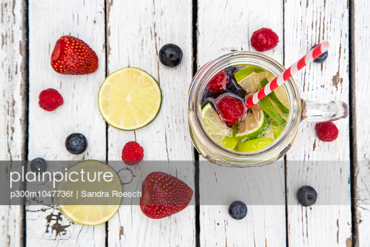 Fruit limonade with fruits and mineral water in glass, drinking straw