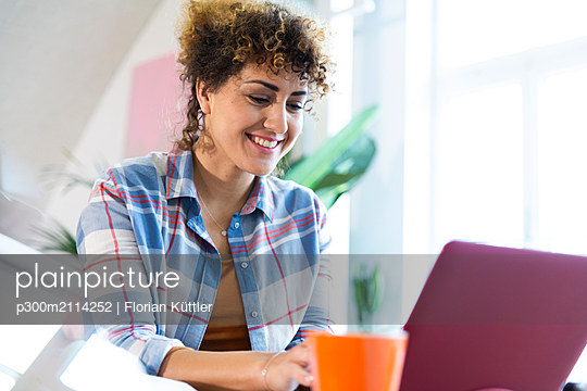 Smiling woman using laptop in office - p300m2114252 by Florian Küttler
