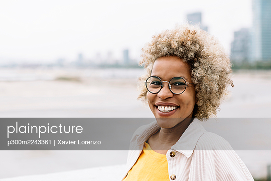 Woman wearing eyeglasses smiling while standing outdoors - p300m2243361 by Xavier Lorenzo