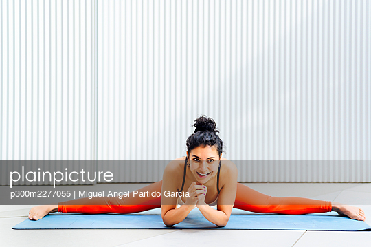 Smiling sportswoman doing splits on exercise mat - p300m2277055 by Miguel Angel Partido Garcia