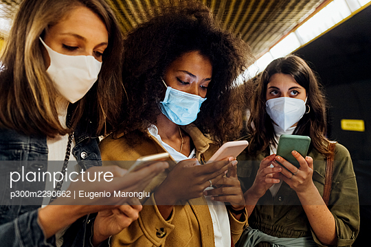 Friends with protective face mask using mobile phone in underground - p300m2290662 by Eugenio Marongiu
