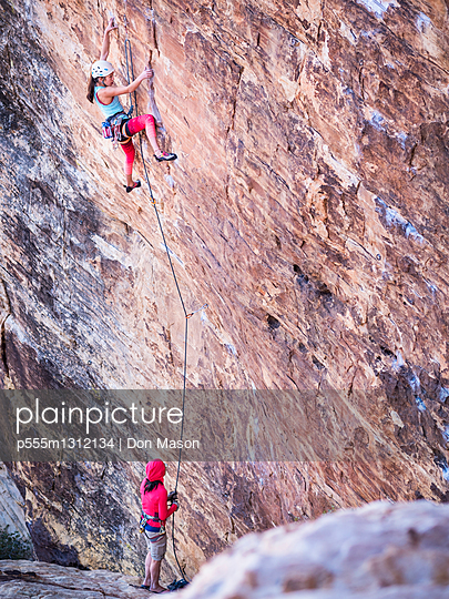 Mother belaying daughter rock climbing on cliff - p555m1312134 by Don Mason