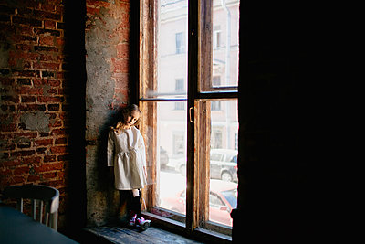 Little girl in a white dress standing by on a window sill - p1414m2044905 by Dasha Pears