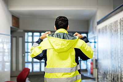 Rear view of auto mechanic student wearing reflective jacket in workshop - p426m1130948f by Maskot