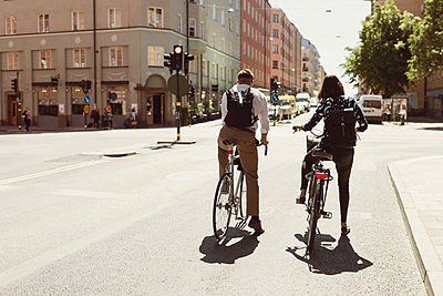 Rear view of business colleagues riding bicycle on city street - p426m1196689 by Maskot