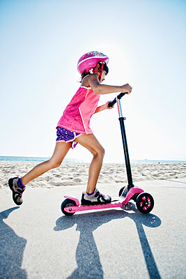 Mixed race girl riding scooter at beach - p555m1305536 by Peathegee Inc