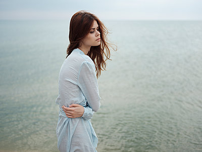 Troubled Caucasian woman standing near ocean - p555m1523029 by Dmitry Ageev