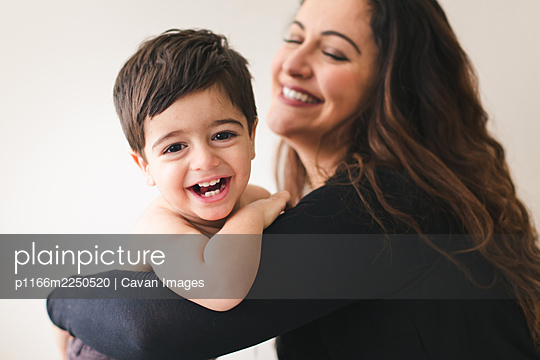 Smiling mom and son being playful, son looking at camera. - p1166m2250520 by Cavan Images
