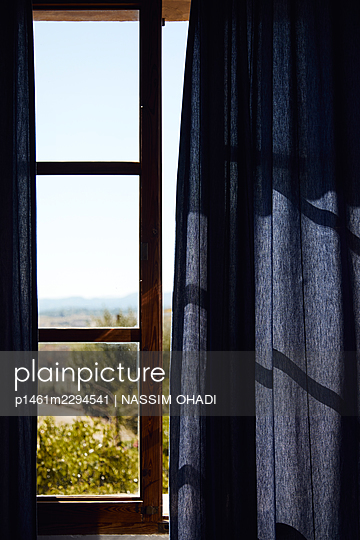 Window with a blue curtain - p1461m2294541 by NASSIM OHADI