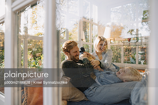 Happy family having fun in sunroom at home - p300m2166628 by Kniel Synnatzschke