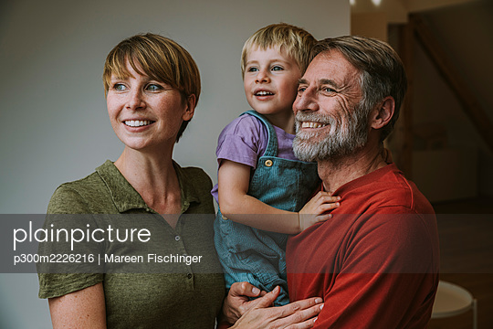 Smiling father carrying son while mother looking away standing at home - p300m2226216 by Mareen Fischinger