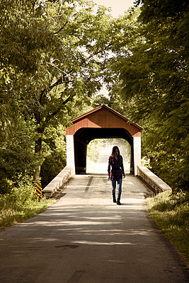 Woman against roofed bridge - p1248m1491860 by miguel sobreira