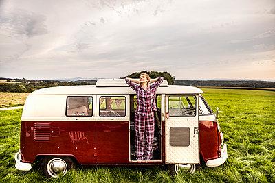 Woman in pyjama stretching in a van in rural landscape - p300m2069789 by Jo Kirchherr