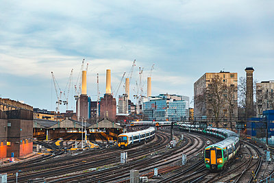 United Kingdom, England, London, view of railtracks and trains in the evening, former Battersea Power Station and cranes in the background - p300m2069968 by William Perugini