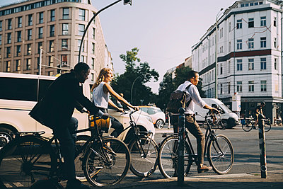 Full length of business colleagues riding bicycles against building in city - p426m2169390 by Maskot