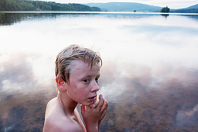 Wet Boy Standing In Front Of Lake  - p847m1529229 by Mikael Andersson