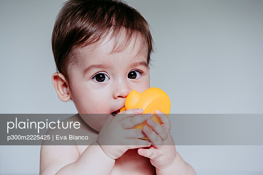 Cute little boy putting toy in his mouth while sitting at home - p300m2225425 by Eva Blanco